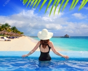 10489414-black-swimsuit-woman-rear-view-in-a-pool-with-direct-view-to-tropical-Caribbean-sea-Stock-Photo
