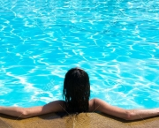 18510649-Portrait-of-young-woman-sitting-in-swimming-pool-Stock-Photo