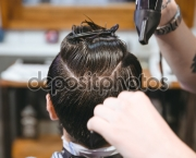 Hairstylist drying hair of male client using hairdryer and comb