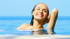 stock-footage-beaufitul-woman-resting-in-infinity-swimming-pool